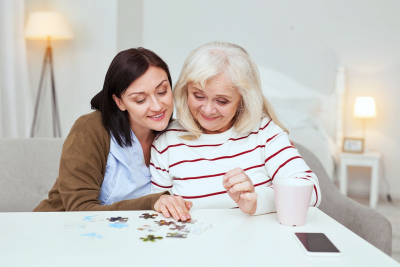 caregiver and senior woman playing puzzle